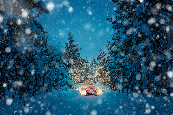 View of snow in blue twilight from windscreen of a vehicle