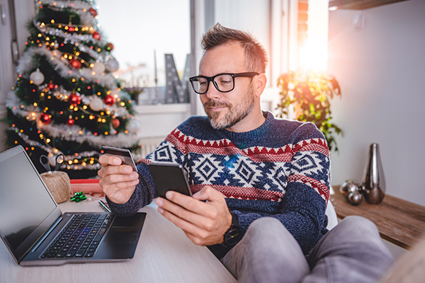 Man at home wearing a Christmas jumper holding a tablet and a mobile with a laptop next to him and a Christmas tree in the background