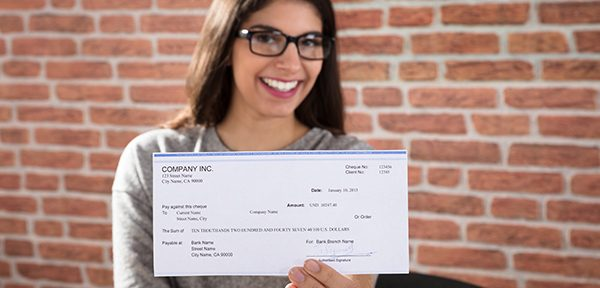 Lady with long hair and glasses, smiling into the camera and holding out a pay cheque
