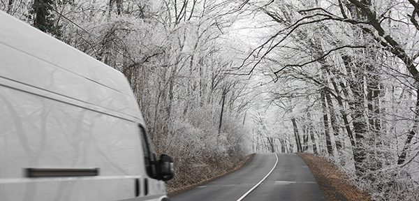 wintry white scene and a white van driving on the icy road