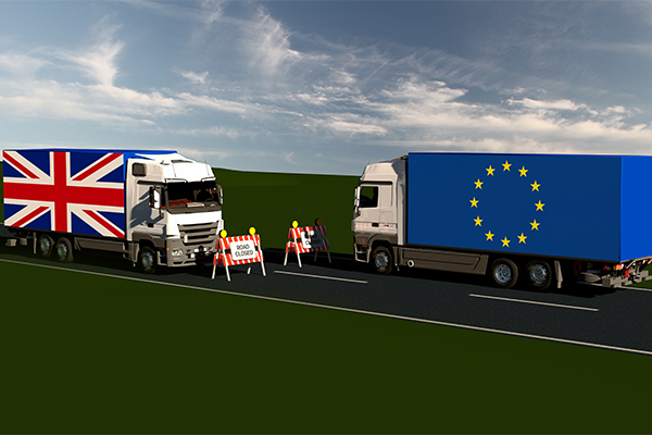 Brexit and trade models of a Union Jack lorry and an EU lorry with a road block in the middle