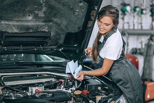 VOR woman in overalls checking van oil