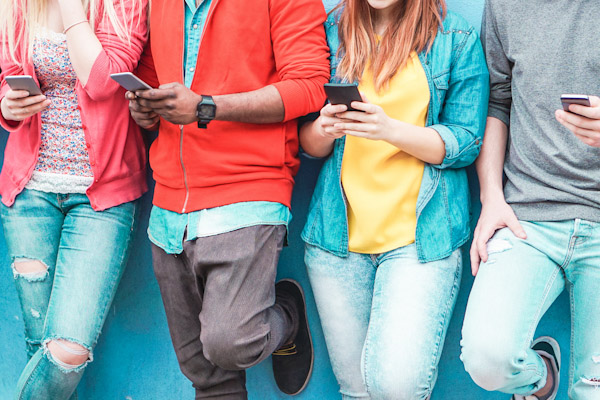 Young adults lined up holding mobile devices
