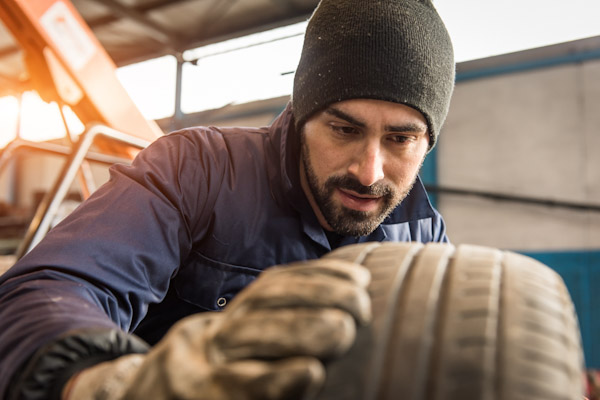 Garage mechanic checks tyres