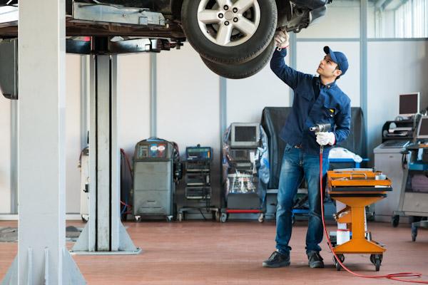 Garage mechanic checks tyres o a jig