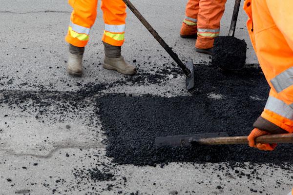road builders mending a pothole