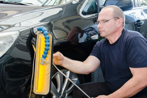 Man fixing a dent made by a reversing vehicle