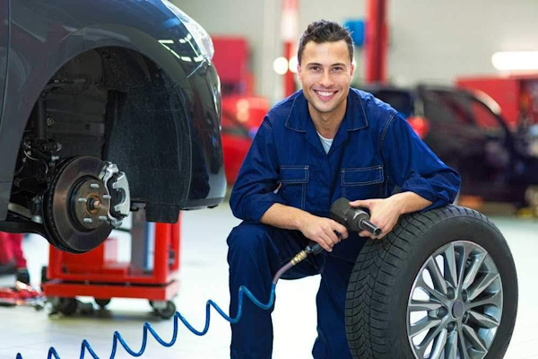 Smiling mechanic fixing a tyre